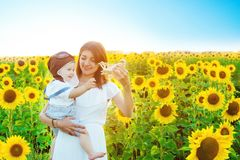 Happy family concept. Beautiful young mother and baby in yellow sunflowers on nature in summer with wooden airplane toy royalty free stock photography