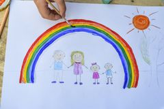 Happy family concept. Child draws on a sheet of paper: father, mother, boy and girl hold hands against background of rainbow and. Sunny sky. Close-up royalty free stock photography