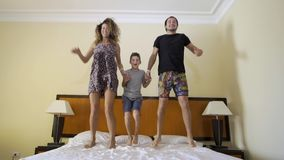 Happy family with little son jumping on bed at home stock footage