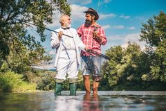 Happy family concept - father and son together. Fly angler on the river. Fishing in river. Man fishing. Generations men stock photo