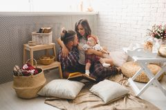 Happy young family mother, father and daughter playing on carpet at home. stock images