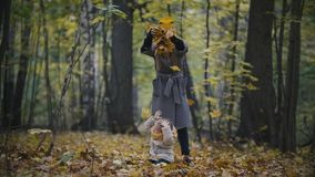 Happy family concept - little daughter with her mother plays with yellow leaves in autumn park, slow-motion stock video