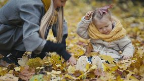 Happy family concept - little daughter with her mother plays with yellow leaves in autumn park stock video footage