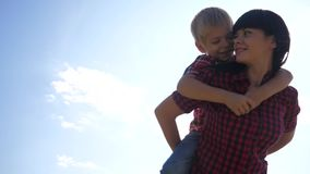 Happy family concept. mom and son cuddle cheerful carefree happy smiling lifestyle . happy family little boy rides an. Happy family concept. mom and son cuddle stock video footage