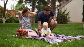 Happy family concept. Mother and son are sitting on plaid, enjoing picnic outdoors. Father brings some cones for his son. Picnic basket. Green park. Slow stock video footage