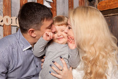 Happy family concept. Parents kissing baby. Happy family concept. Parents kissing their baby Stock Photography
