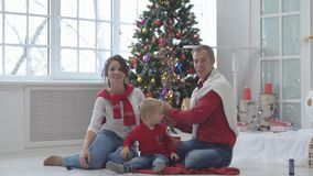 Happy family with confetti on background of Christmas tree with gifts. Happy new year and christmas concept stock video footage