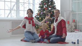 Happy family with confetti on background of Christmas tree with gifts. New Year holidays stock video