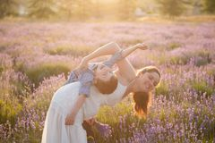 Happy family consisting of beautiful mother and adorable child playing togehter leisure games among summer field of flowers outdoo royalty free stock photography