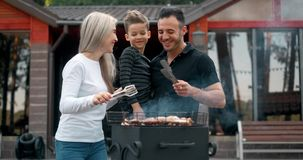 Happy family cook meat on grill. Father and mother with son fry sausages on grill and smiling. Slow motion
