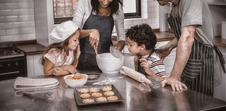 Happy family cooking biscuits together. In kitchen at home royalty free stock image
