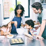 Happy family cooking biscuits together stock photography