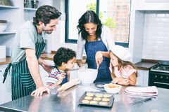 Happy family cooking biscuits together stock photos