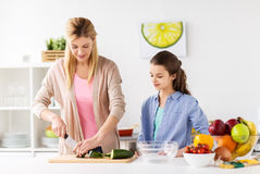 Happy family cooking dinner at home kitchen. Cooking food, healthy eating, family and people concept - happy mother and daughter chopping vegetables for dinner Stock Images