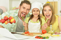 Happy family cooking in kitchen. Portrait of happy family cooking in kitchen with laptop royalty free stock photo