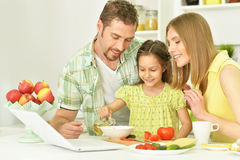 Happy family cooking in kitchen. Portrait of happy family cooking in kitchen with laptop stock photos