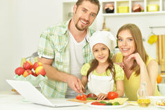 Happy family cooking in kitchen. Portrait of happy family cooking in kitchen with laptop royalty free stock image