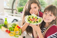 Happy family cooking salad. Vegetarian meal at kitchen royalty free stock photo