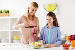 Happy family cooking salad at home kitchen. Food, healthy eating, family and people concept - happy mother and daughter cooking and adding olive oil to vegetable Stock Images