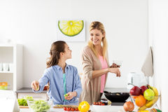 Happy family cooking salad at home kitchen. Healthy eating, family and people concept - happy mother and daughter cooking vegetable salad and frying food for Royalty Free Stock Photo