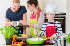 Family cooking together in kitchen royalty free stock photo