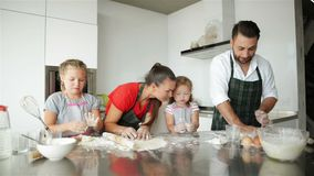 Happy Family Cooking Together. Young Daughters Are Helping To Their Parents. They Have a Lot of Fun. stock footage