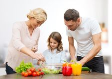 Happy family cooking vegetable salad for dinner