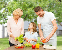 Happy family cooking vegetable salad for dinner. Vegetarian food, culinary, happiness and people concept - happy family cooking vegetable salad for dinner over Stock Images