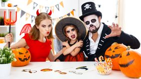 Happy family in costumes getting ready for halloween at home Royalty Free Stock Photo