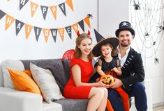 Happy family in costumes getting ready for halloween Royalty Free Stock Photo