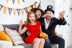 Happy family in costumes getting ready for halloween at home stock image