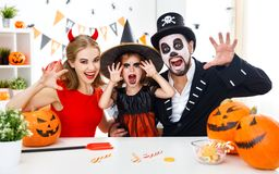 Happy family in costumes getting ready for halloween at home Stock Images