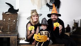Happy family in costumes holds paper pumpkins on celebration of Halloween. Family has fun in Halloween time. Happy stock footage