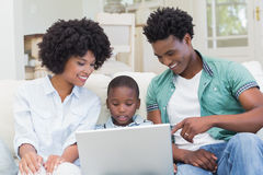 Happy family on the couch with laptop Stock Photos