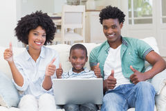 Happy family on the couch with laptop Stock Images