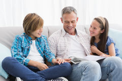 Happy family on the couch reading storybook Stock Photos