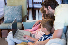 Happy family on the couch together using laptop Royalty Free Stock Photos