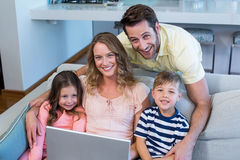 Happy family on the couch together using laptop. At home in the living room Stock Photos