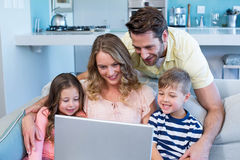 Happy family on the couch together using laptop. At home in the living room Stock Images