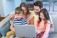 Happy family on the couch together using laptop. At home in the living room Royalty Free Stock Photos