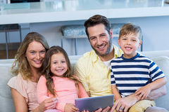 Happy family on the couch together using tablet Stock Images