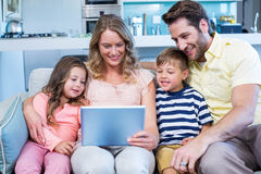 Happy family on the couch together using tablet Royalty Free Stock Photos