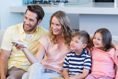 Happy family on the couch watching tv. At home in the living room Stock Photography
