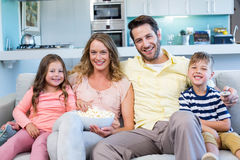Happy family on the couch watching tv. At home in the living room Royalty Free Stock Photography