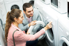 Happy family couple buying new clothes washer Royalty Free Stock Photo