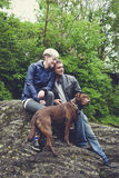 Happy family couple with dog hiking traveling in the forest on a sunny day Stock Photo