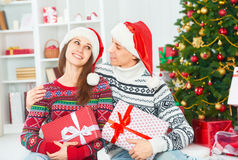 Happy family couple with a gift on Christmas at home Royalty Free Stock Photos
