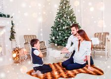 Happy family couple give gifts in the living room, behind the decorated Christmas tree, the light give a cozy atmosphere. New Year and Xmas theme royalty free stock images