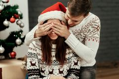 Happy family couple, handsome man preparing a christmas present royalty free stock image