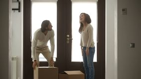 Happy family couple holding boxes opening door entering new house